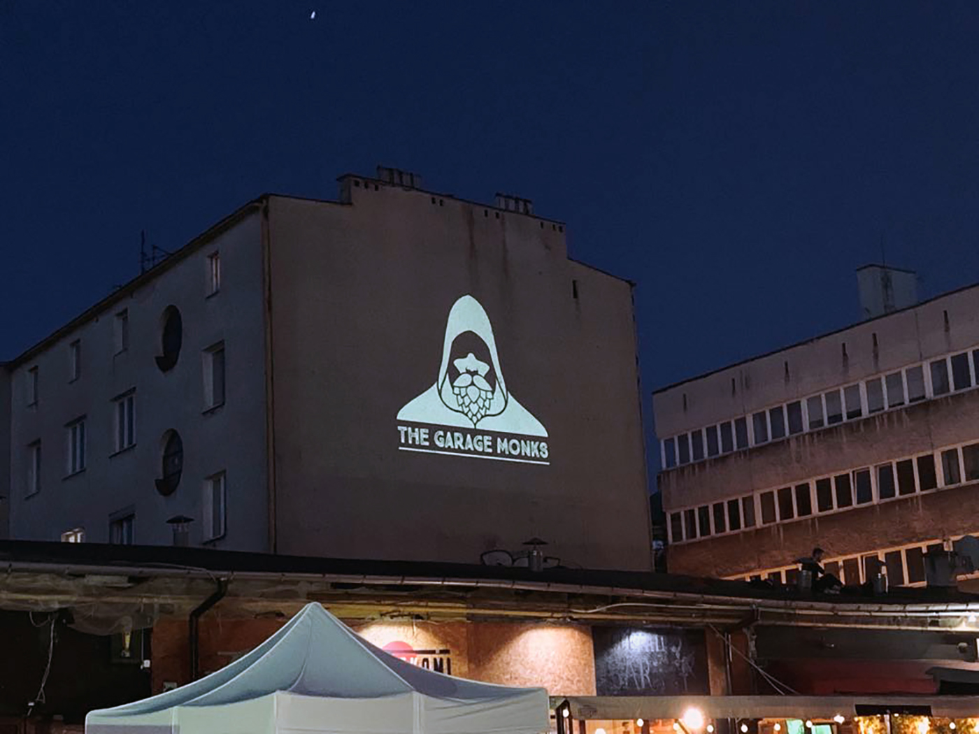 The Garage Monks brewery logo on a building wall by Jakub Cichecki